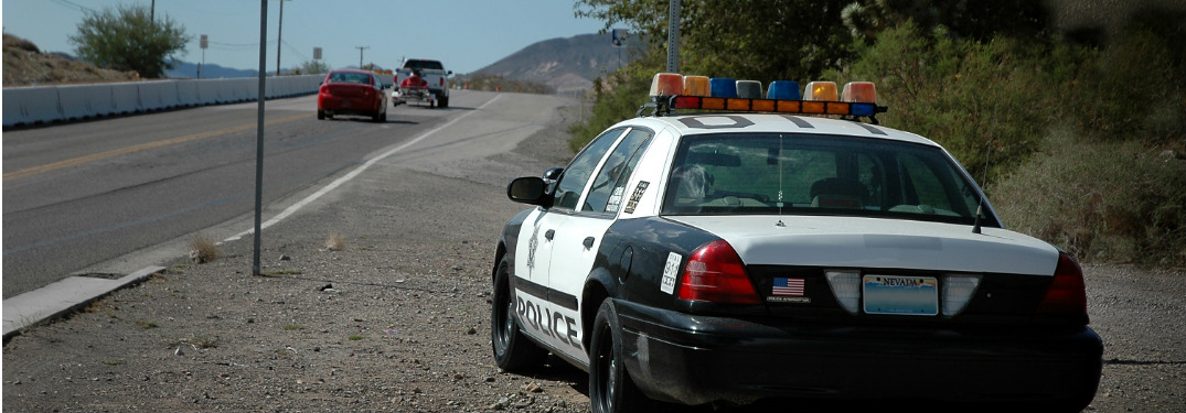 A police car sits beside a highway and watches diligently.