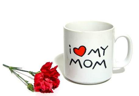 "A mug says. ""I [heart] my mom."" A clipped red rose lays next to it."