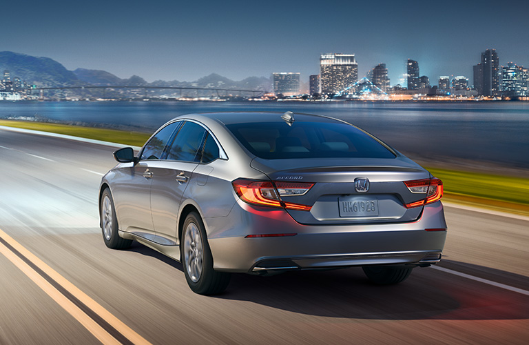 Silver 2019 Honda Accord rides down a highway at late dusk with a city skyline in the background beyond a body of water.