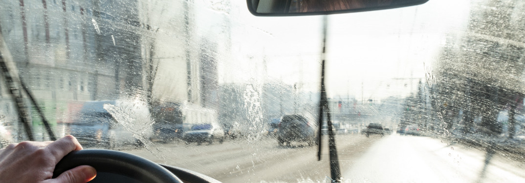 A windshield as seen from inside a car, looking out on a rainy city street ahead.