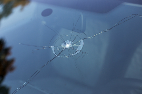 A circular hole from which cracks radiate outward is seen on a windshield. Luckily, as laminated glass, this can be repaired..
