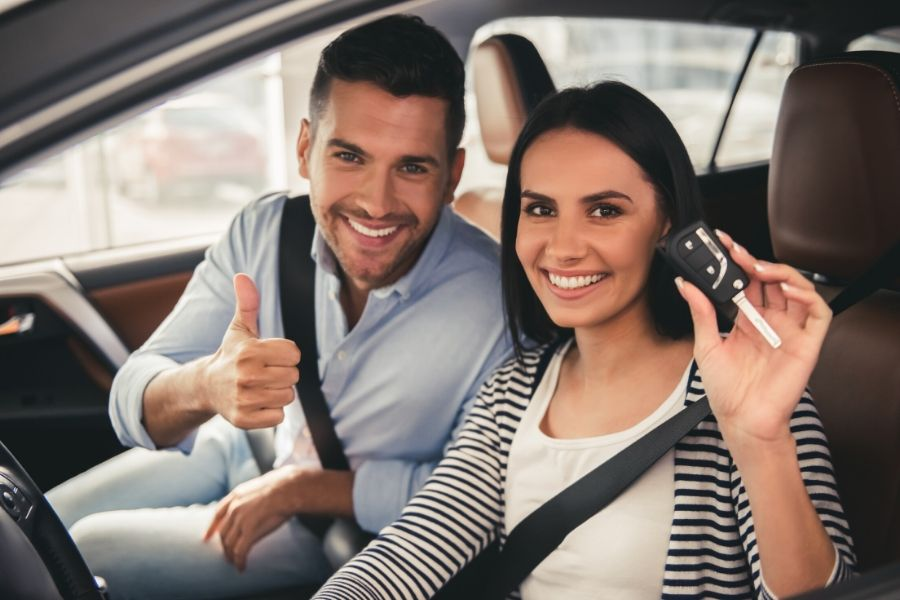 Couple sitting in a car smiling and giving thumbs up while woman holds car key