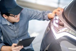 Person inspecting headlight on vehicle