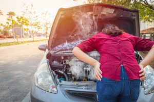 Woman standing in front of overheating car