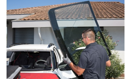 Man replacing windshield carrying it outside family home with brown tile roof