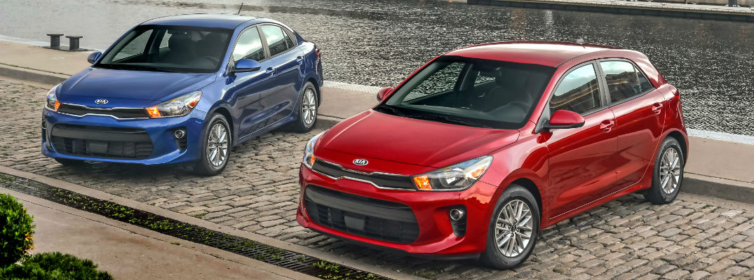 A photo of the sedan and hatchback versions of the 2019 Kia Rio parked by a river.