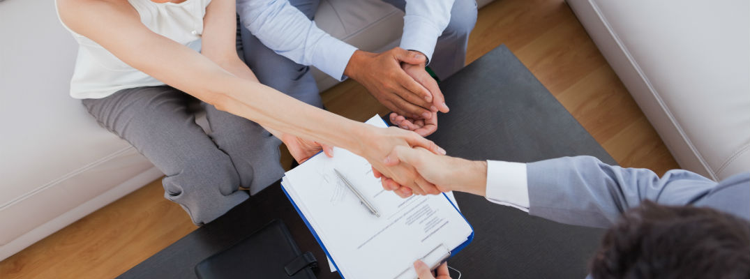 A stock photo of people shaking hands after signing some paperwork.