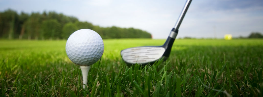 A stock photo of a golf club addressing a golf ball on a tee.