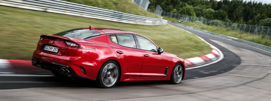 A right profile photo of the Kia Stinger driving on a race track.