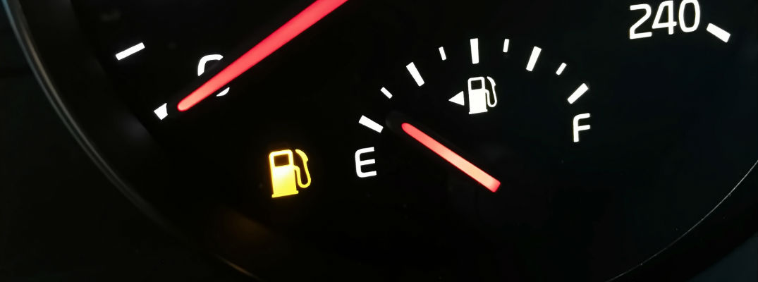 A stock photo of a gas gauge nearly on empty with the low-fuel light turned on.