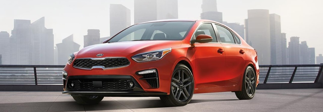 Front driver angle of the 2019 Kia Forte in Fire Orange color with a city skyline in the background