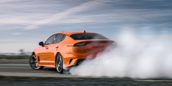 Rear view of orange 2019 Kia Stinger with smoke cloud behind it