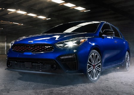 Front driver angle of a blue 2020 Kia Forte with its headlights on in a building