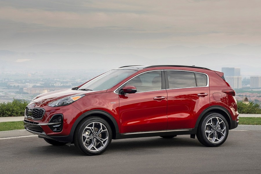 Front driver angle of a red 2020 Kia Sportage parked on a road with a city in the background