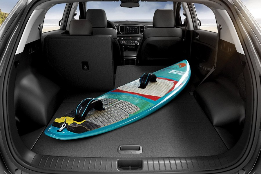 View from rear of the back opened with passenger side seats down and a blue surfboard inside the 2020 Kia Sportage