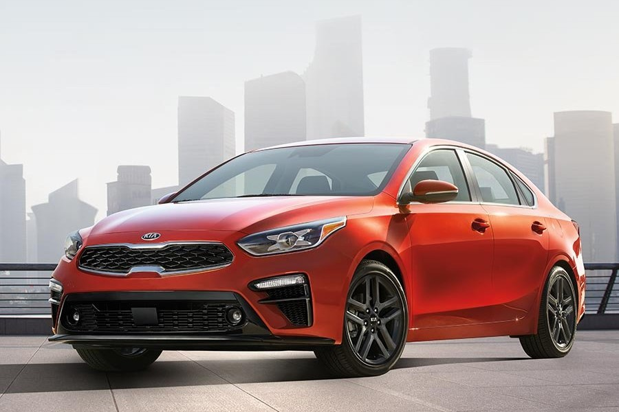 Front driver angle of an orange 2019 Kia Forte with a city skyline in the background