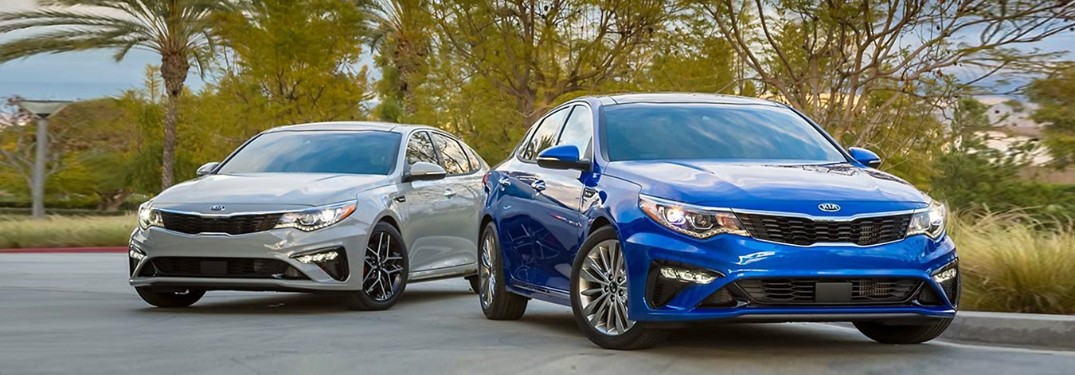 A grey 2019 Kia Optima parked next to a blue 2019 Kia Optima