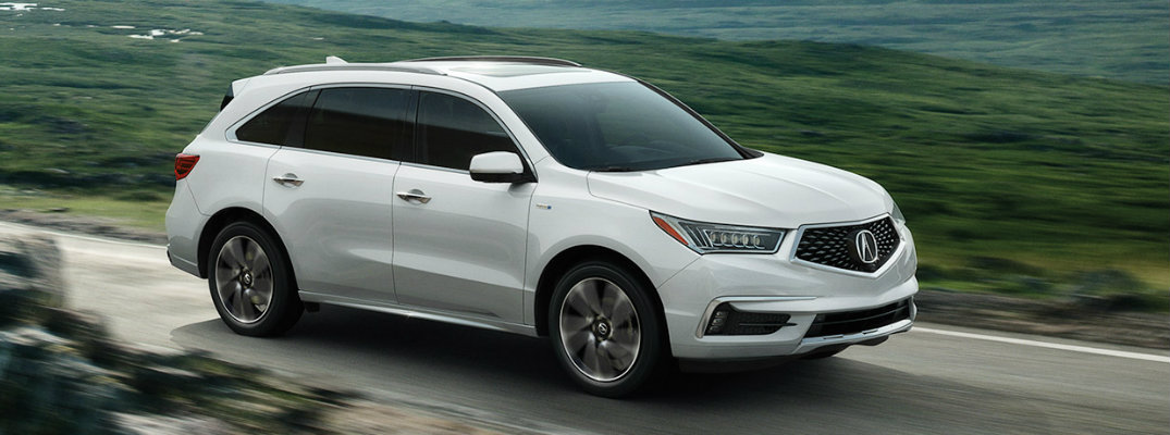 White 2019 Acura MDX driving down empty country road