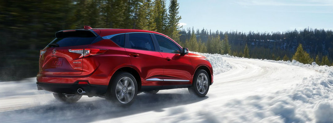 Profile view of red 2019 Acura RDX driving on snowy highway