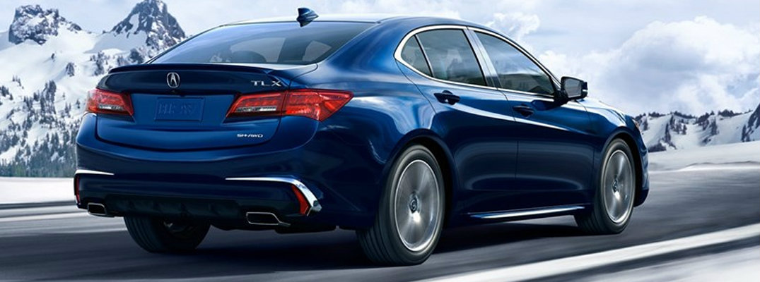 Rear shot of blue 2019 Acura TLX driving on snowy road