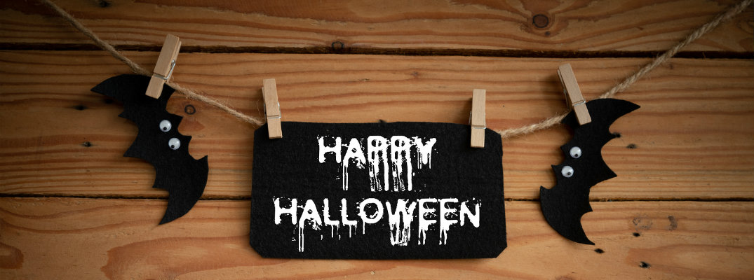 Black Happy Halloween sign hanging from rope with clothespins against a wood background