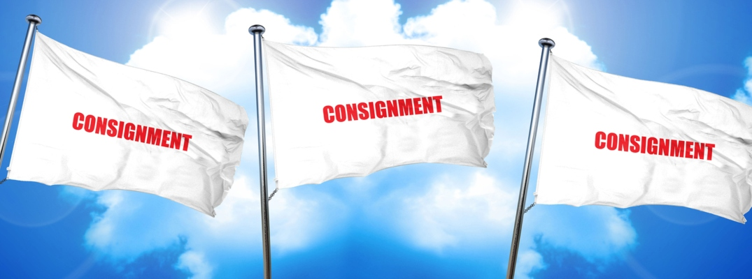 """Image of three white flags blowing in the wind with the word """"consignment"""" in red text"""