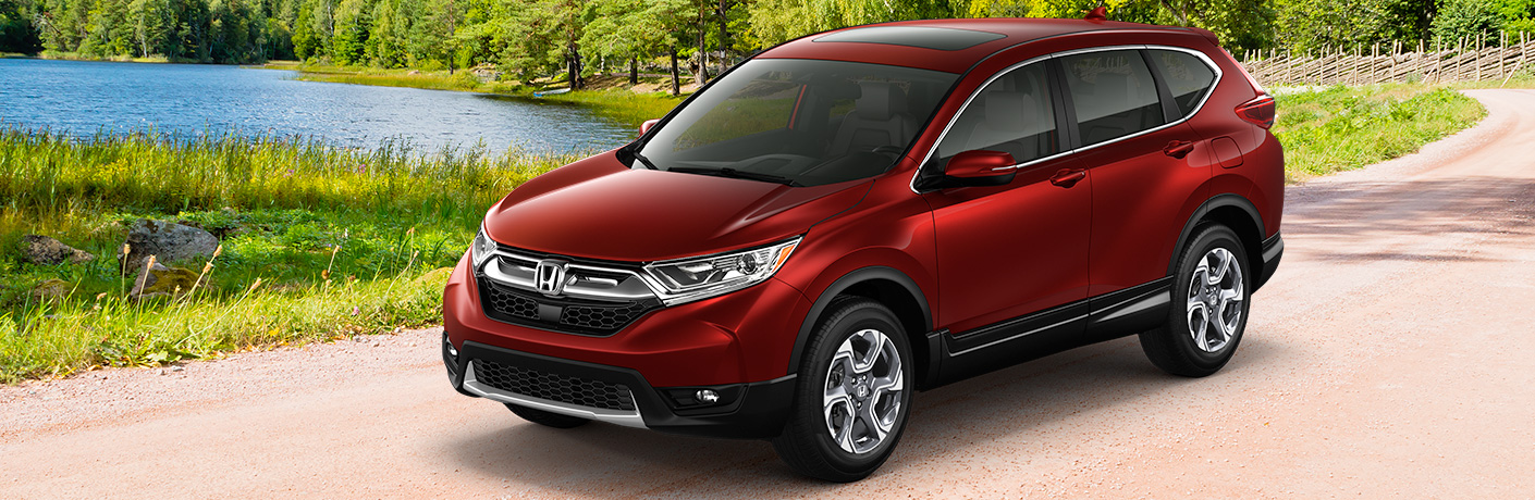 Exterior view of a red 2018 Honda CR-V parked outside near a pond