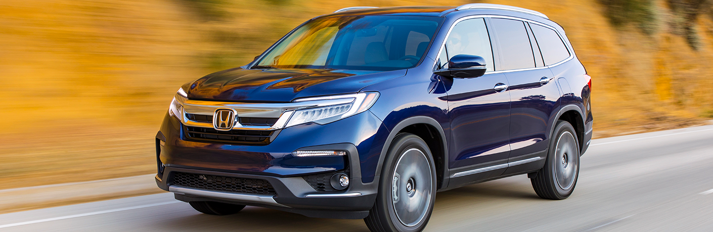 Exterior view of a blue 2019 Honda Pilot driving down a country highway