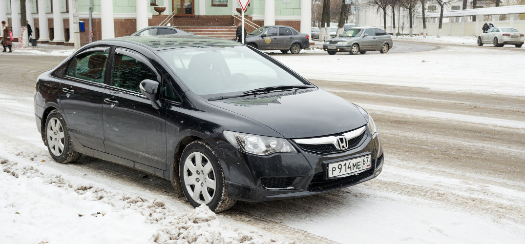 Exterior view of a blue Honda Civic parked on a snow-covered city street