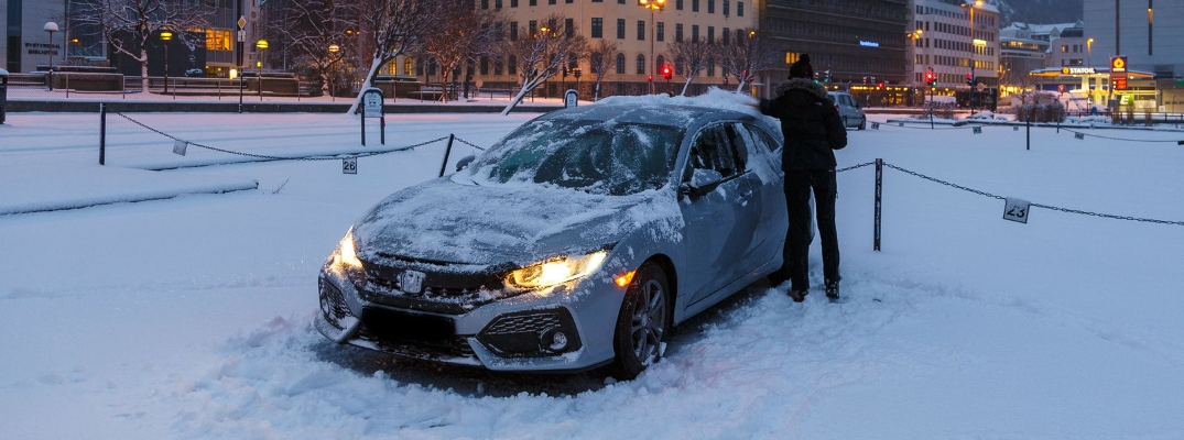 Person cleaning the snow off a white Honda Civic parked on a snow-covered road