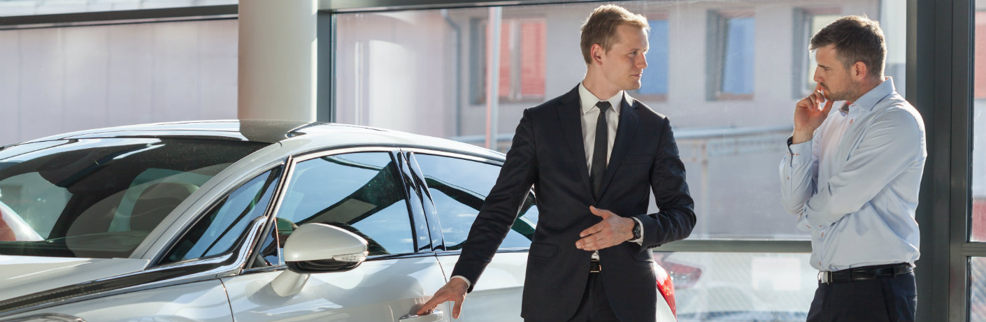 Two men in suits looking at a car
