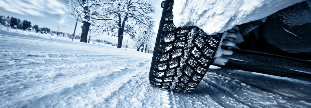 Close-up on the tire of a vehicle as it drives down a snow-covered street.