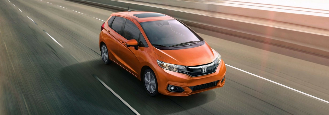 2018 Honda Fit in orange driving on a highway in a city