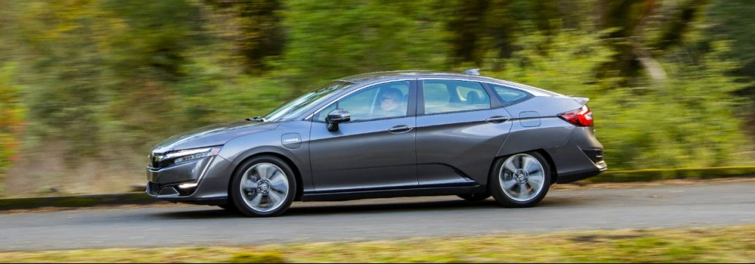 full view of the 2018 Honda Clarity Plug-In Hybrid driving on a country road