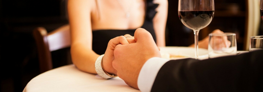 well-dressed couple holding hands at restaurant