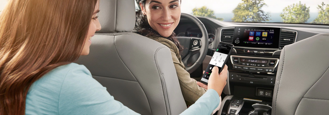 girl in honda vehicle using smartphone