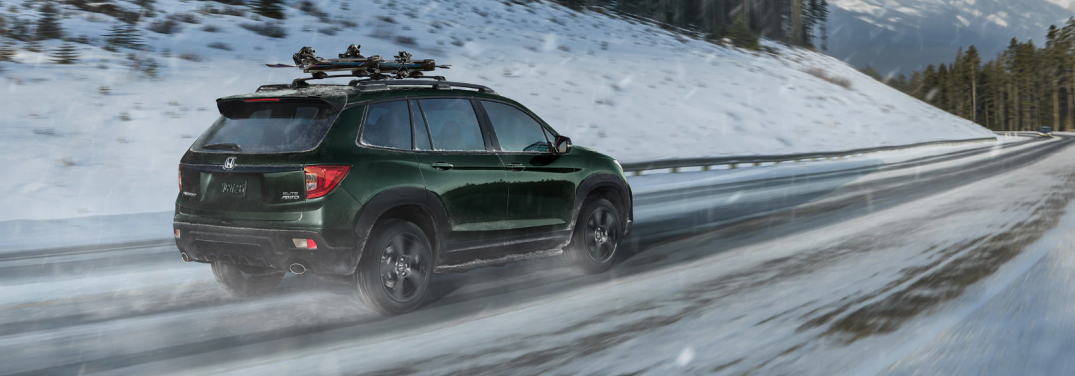 rear view of honda passport driving through a snowy mountain pass
