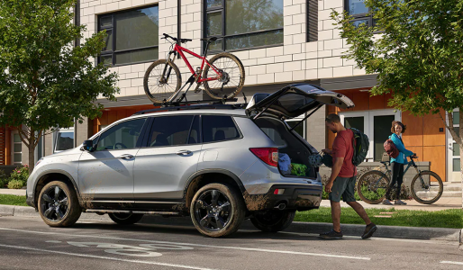 2019 Honda Passport full of mud with bike on roof rack and trunk full of camping gear