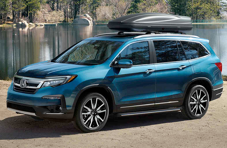 Blue 2019 Honda Pilot with some kind of a boat on its roof, parked out by a lake in nature.