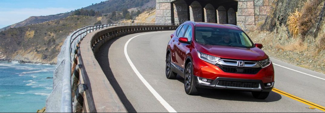 Red 2019 Honda CR-V cruises around a highway curve out by the ocean with the help of it's all-wheel drive feature.