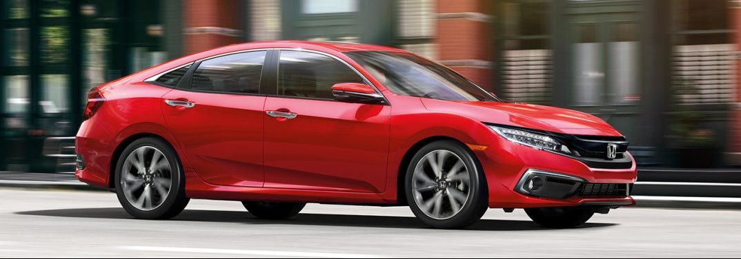 Side view of a red 2019 Honda Civic as it cruises down a city street.