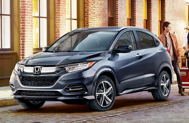 Modern Steel Metallic 2019 Honda HR-V Touring is parked outside a brick building with some containers on wheels behind it.