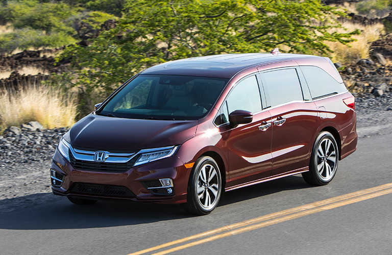 Maroon 2019 Honda Odyssey drives toward us down a country highway.