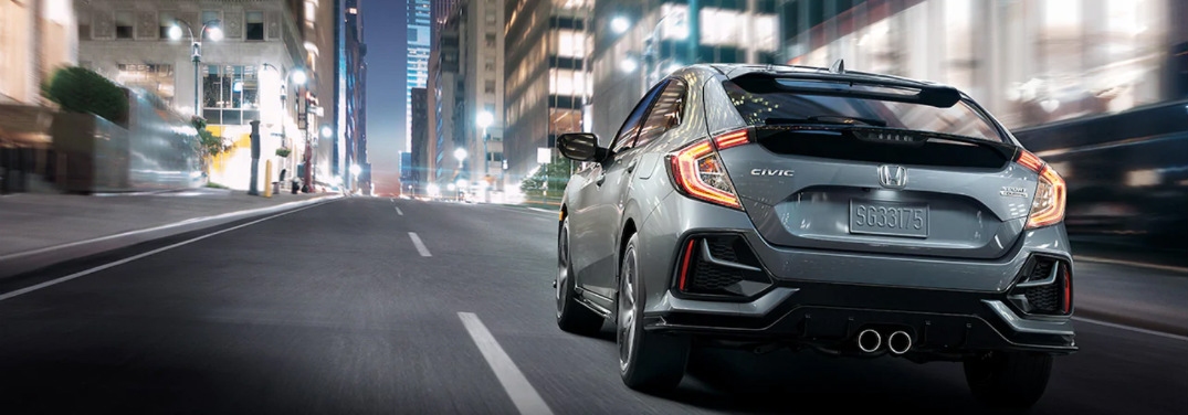 Silver 2020 Honda Civic drives down a city street at night.
