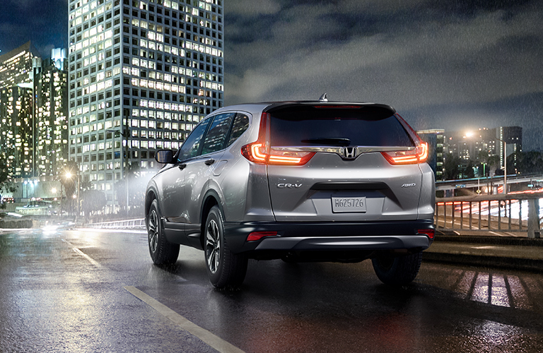 Silver 2019 Honda CR-V drives into a city at night.