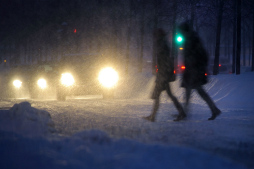Two hunched figures cross the street in the gloom of intense nighttime snow, with a line of headlights approaching.
