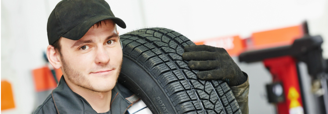 Mechanic carrying tire over his shoulder
