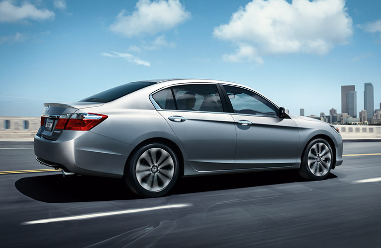Silver 2017 Honda Accord rolls down a highway outside a city, with the skyline in the distance.