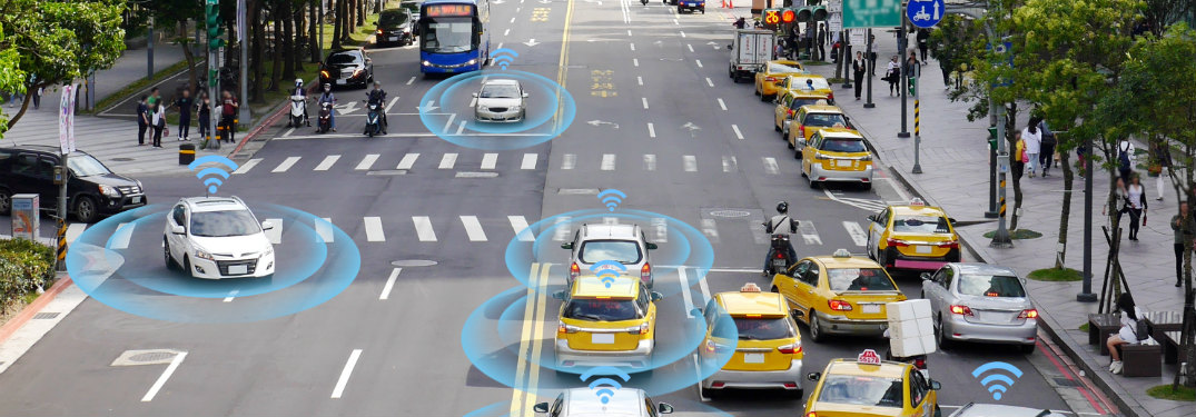 Several self-driving cars drive down a sunny street. Their intelligence is represented by glowing blue circles surrounding them.