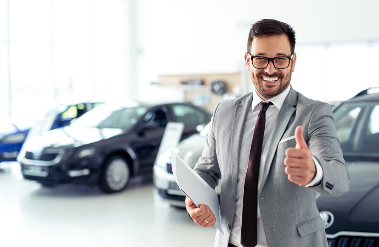 A grinning salesman in a car showroom gives the thumbs up.